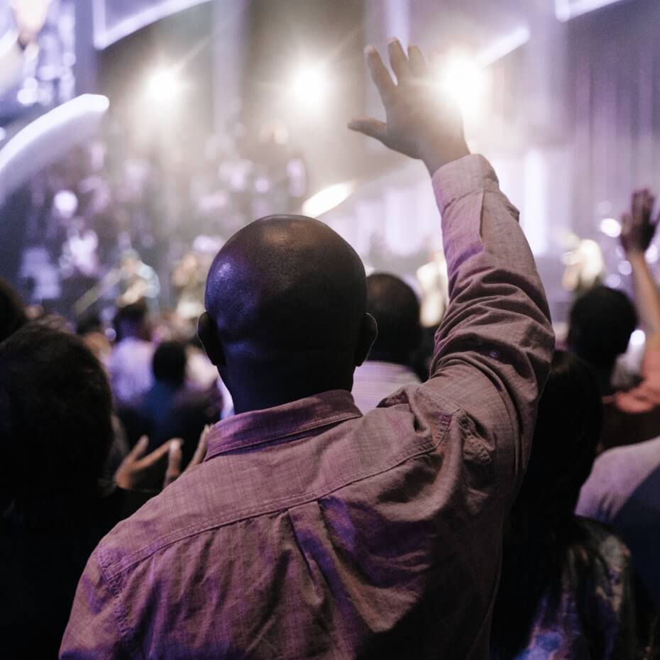 A man raises his hand in worship