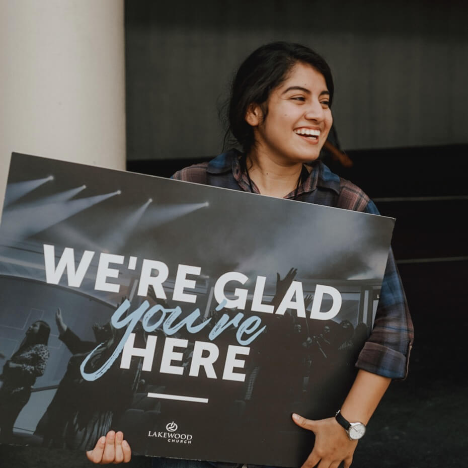 """Greeter holds """"we're glad you're here"""" sign"""