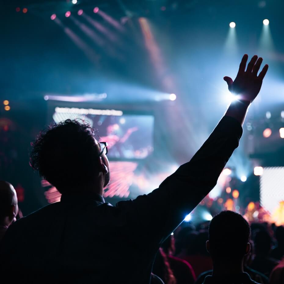 A young adult lifts his hand in worship