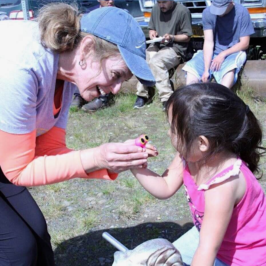 A volunteer handing a toy to a child during a mission trip to Alaska.