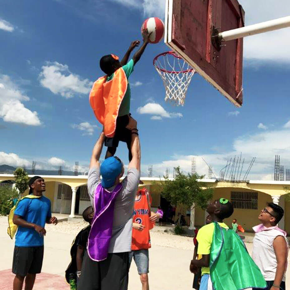 A volunteer helps a child reach a basketball hoop during a mission trip to Haiti.