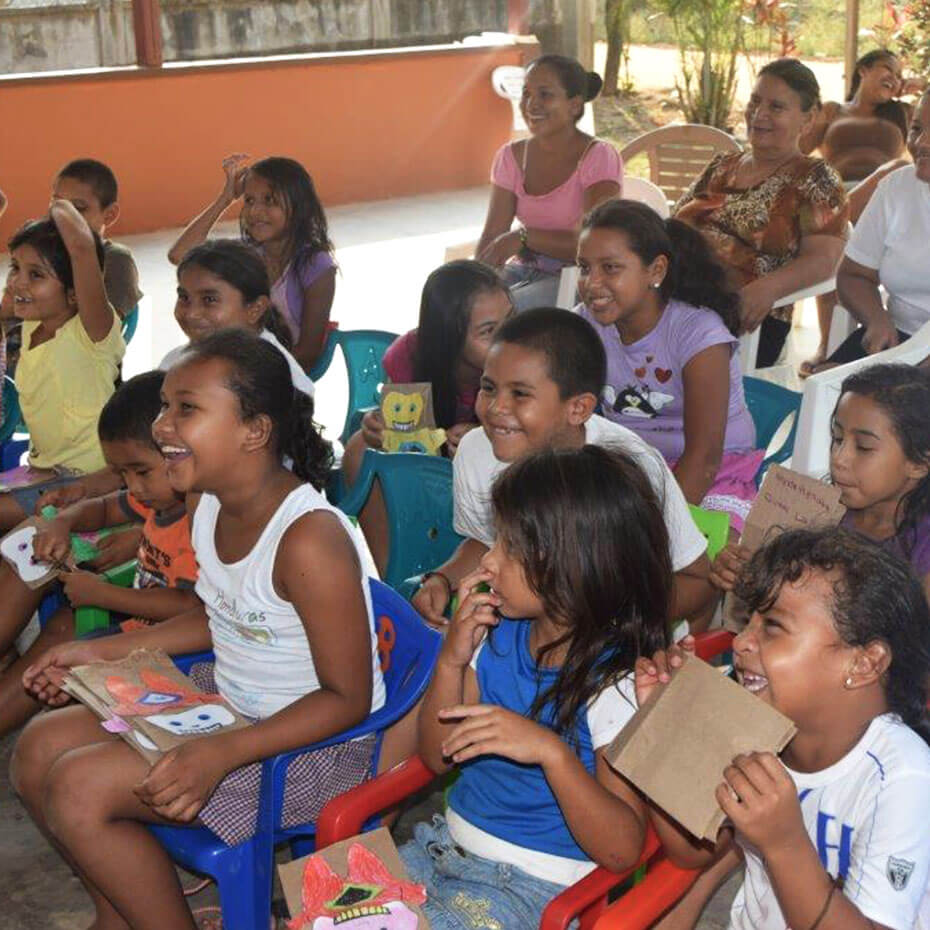 A group of kids laughing while watching a presentation during a mission trip to Honduras.