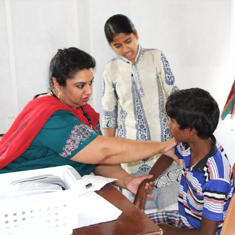 A volunteer checks the blood pressure of a patient during a medical mission trip to India.