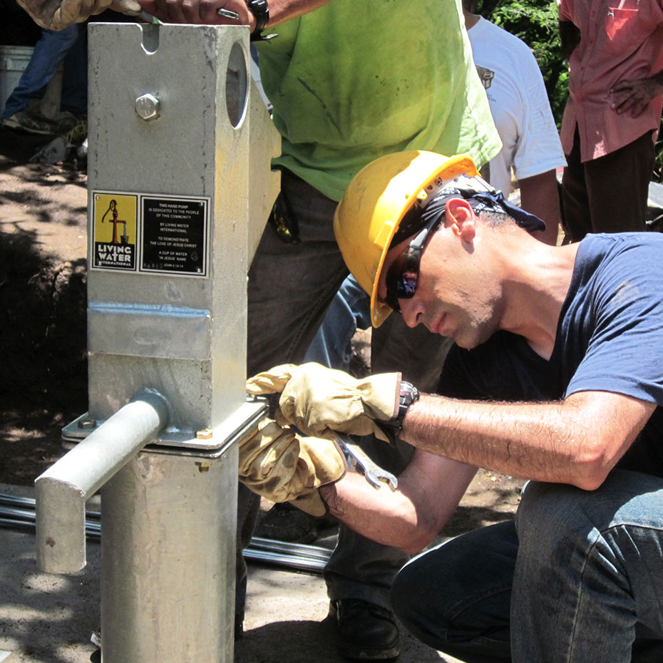 A volunteer puts the finishing touches on a Living Water well during a mission to El Salvador.
