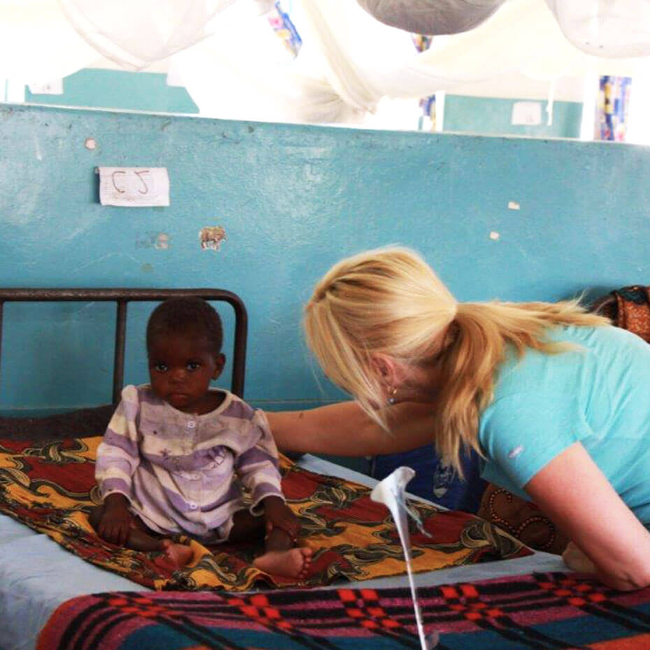 A nurse prays over a child during a mission trip to Kenya.
