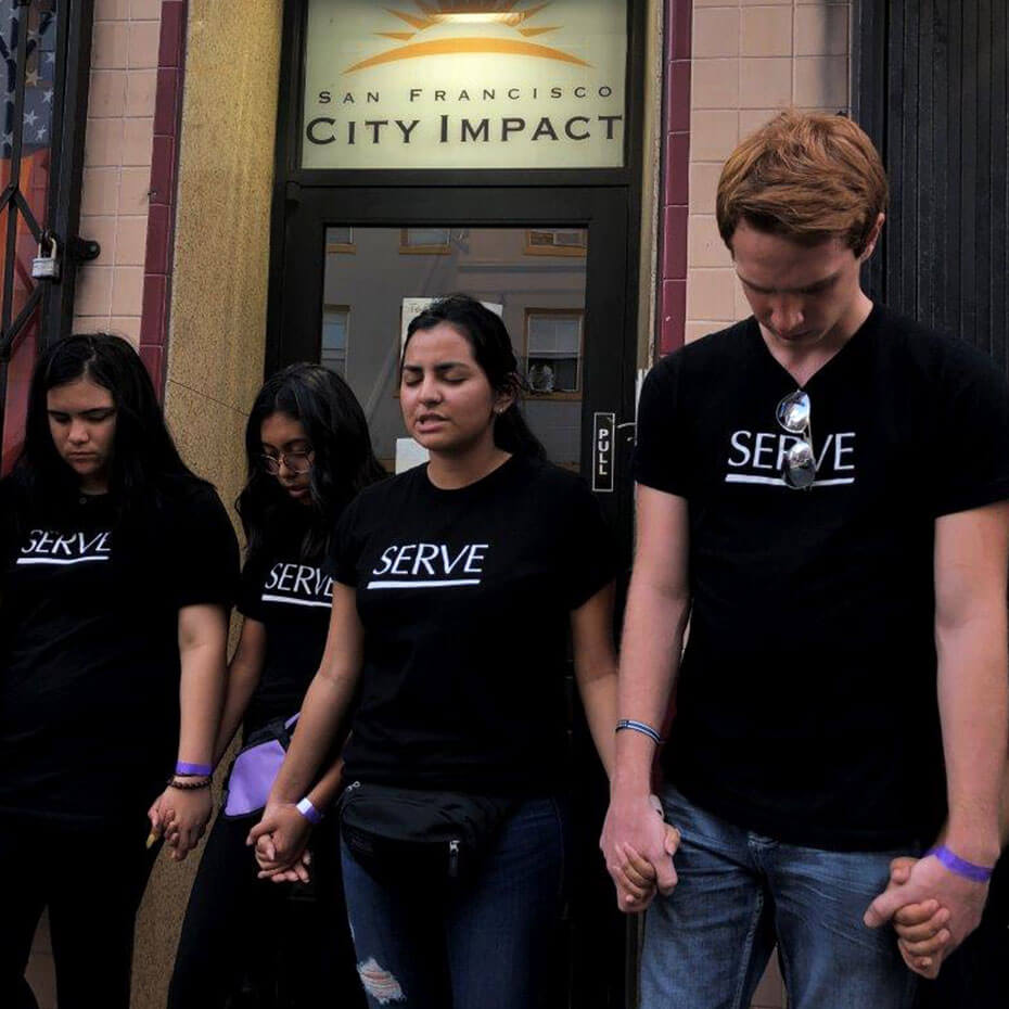 A group of teens prays in front of a building during a mission trip to San Francisco.