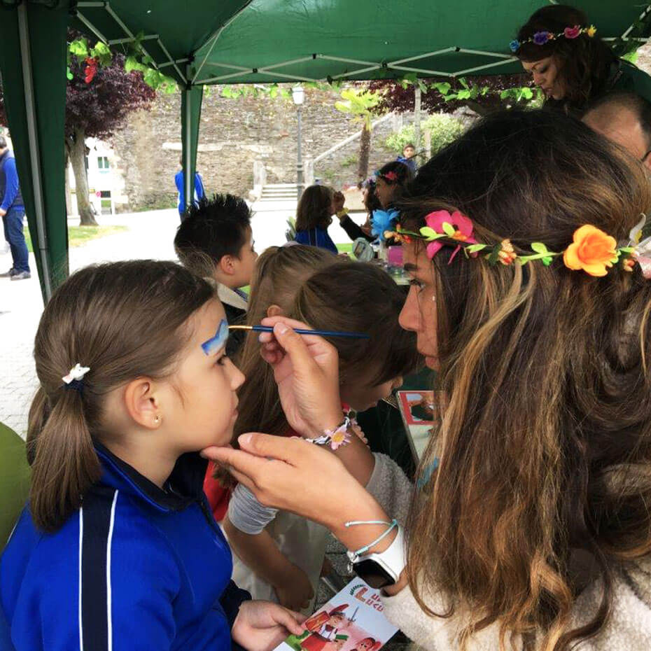 A volunteer helps with face paint for kids during a mission trip to Spain.