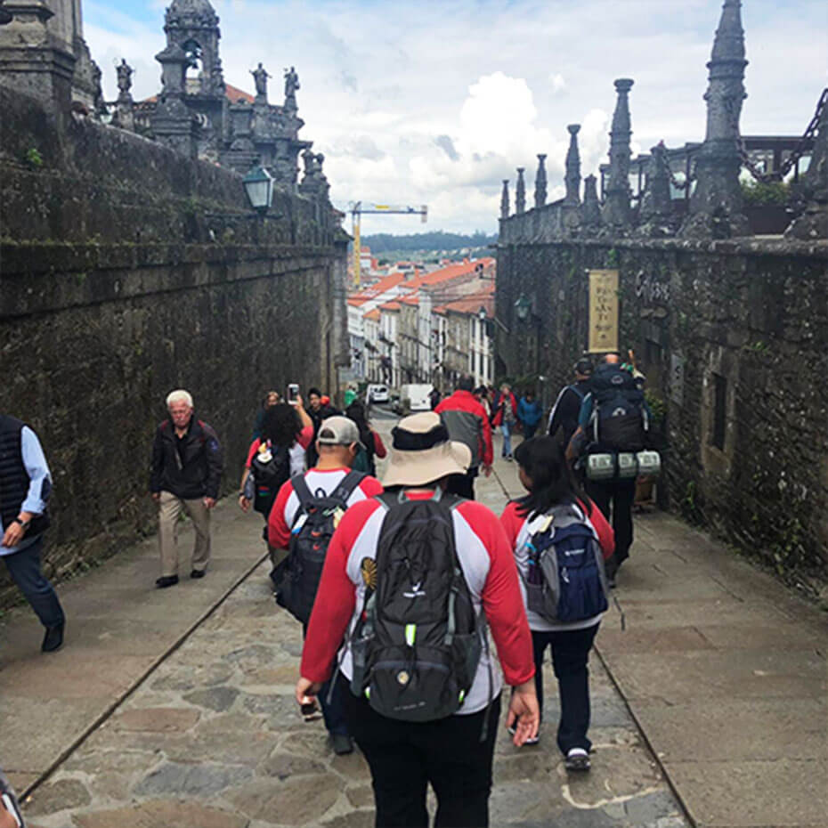 A group of volunteers walks down a stone pathway during a mission trip to Spain.