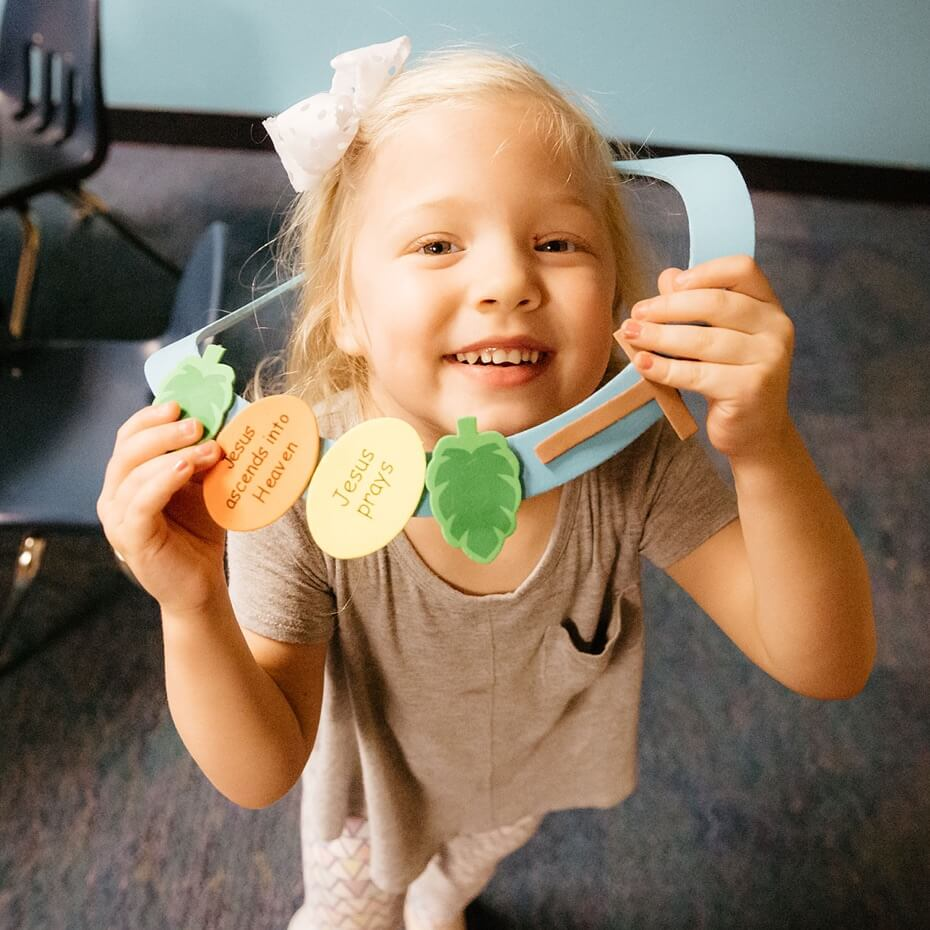 A child shows off her art from the arts and crafts session that day, where she also learned about Jesus.