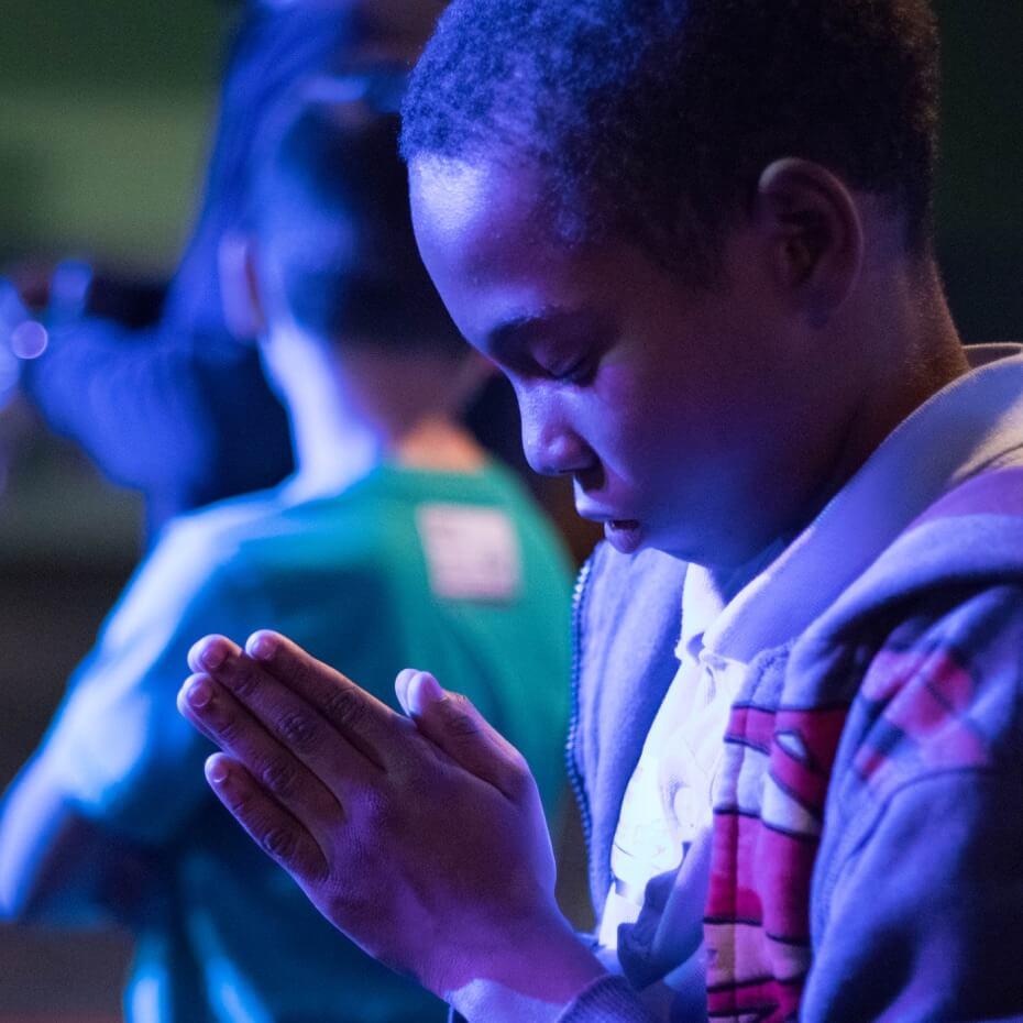 A child praying during KidsLife's prayer time