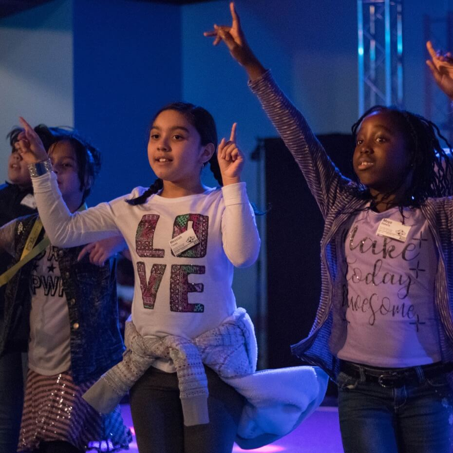 A group of kids raising their hands during an interactive worship experience