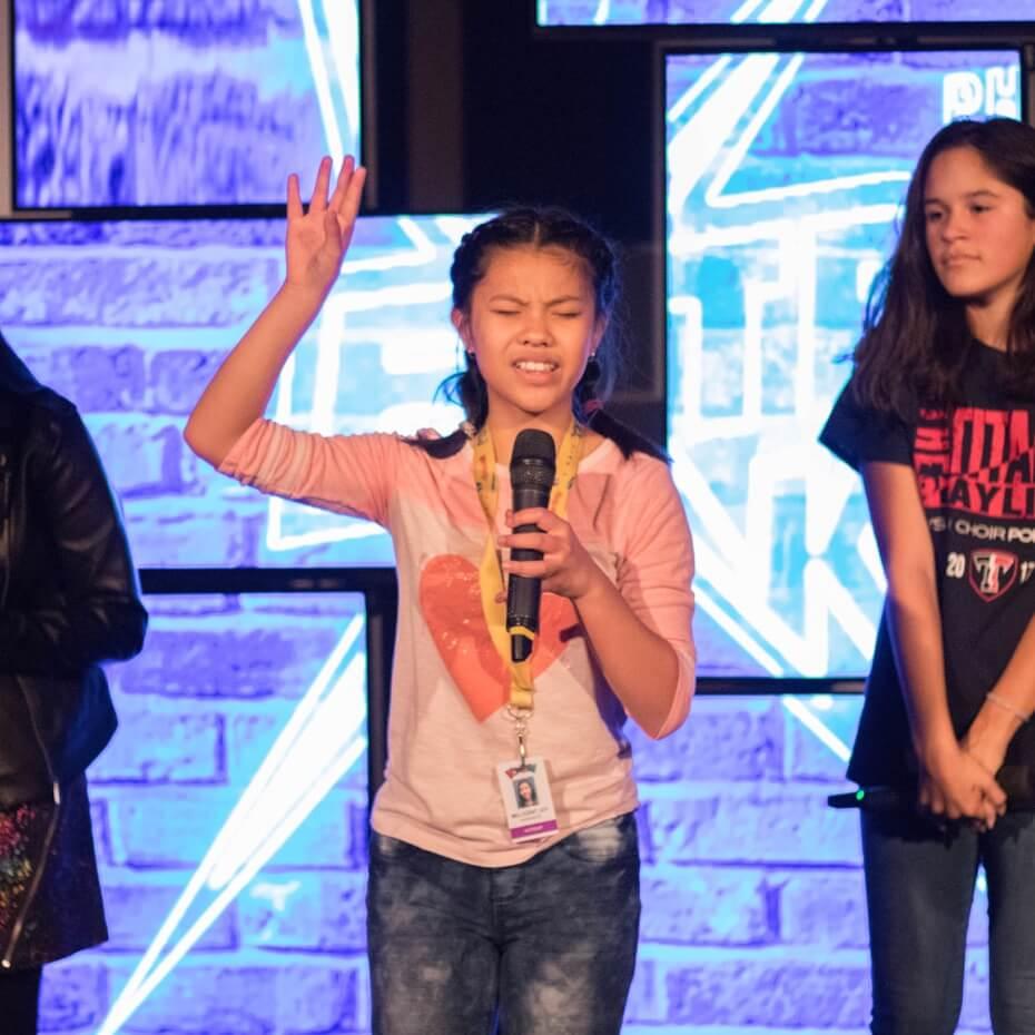 Young member of KidsLife leading prayer.