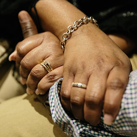 A couple holding hands with their wedding rings visible