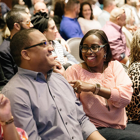 A husband and wife laughing together in the audience of the Spark Marriage Conference at Lakewood Church